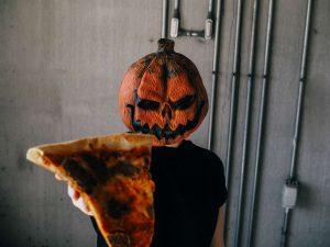 pumpkin head holding pizza