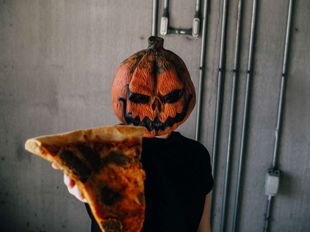 pumpkin head guy holding up a slice of pizza