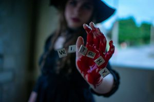 """witch with bloody hand and scabble tiles spelling out """"witchy"""""""