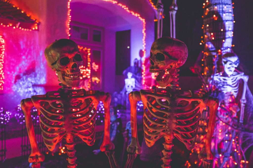 pair of skeletons in front of Halloween house