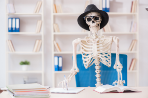 skeleton wearing a dress hat and glasses writing in notebook