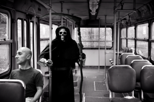angel or death wielding a sickle riding a bus behind man seated