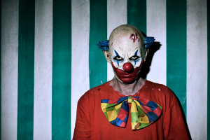 scary clown staring at you in front of green and white striped wall