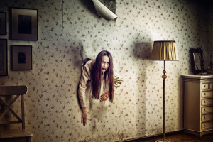 scare-actor coming out of the wall in hunted house living room