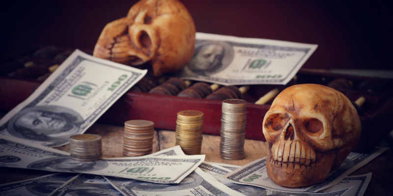 plastic skulls paying on a table amidst piles of cash and coins