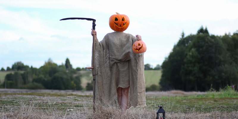 scarecrow with pumpkin head holding a sickle and a jack-o-lantern in a field with smiling face