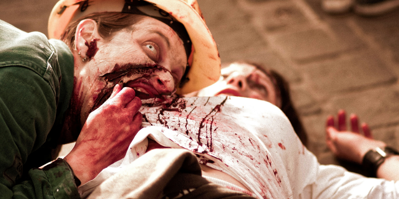 zombie looking up at camera with one eye while attacking a person eating their guts