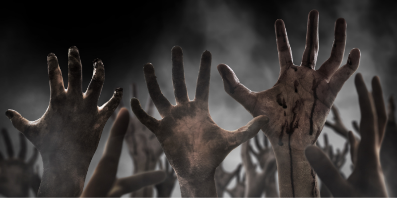 zombie hands coming out of the ground in a graveyard