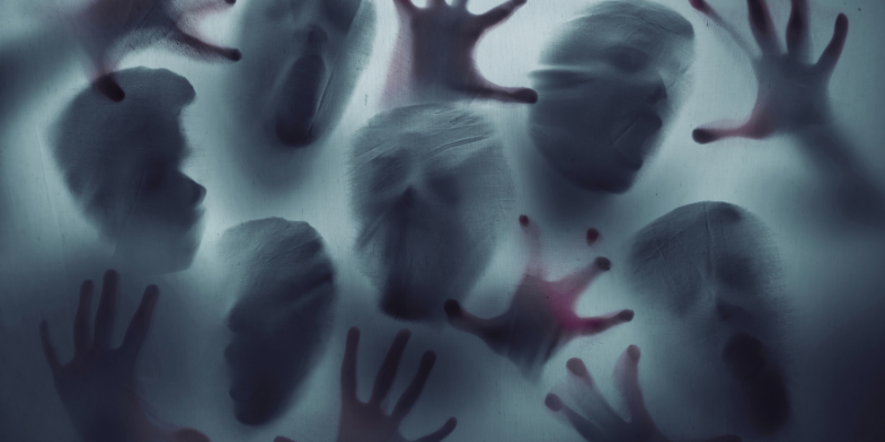 faces and hands pressing up against a translucent piece of fabric trying to get through
