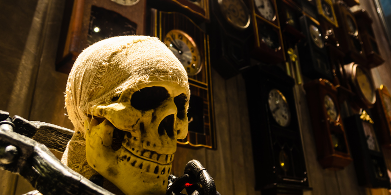 skeleton with neck chained to a shackle in front of a wall of old clocks