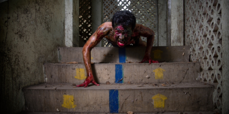 bloody zombie climbing down stairs to get you