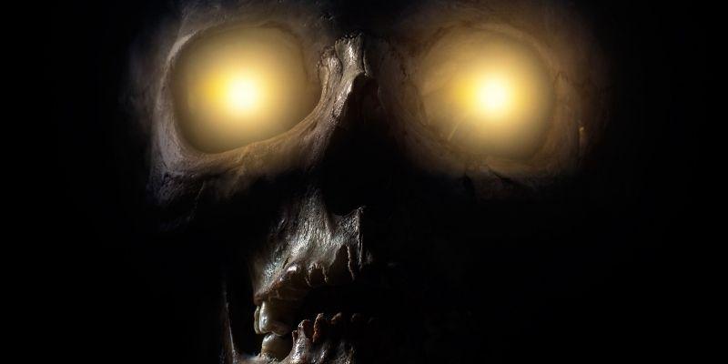 skull with yellow lights shining through eye sockets