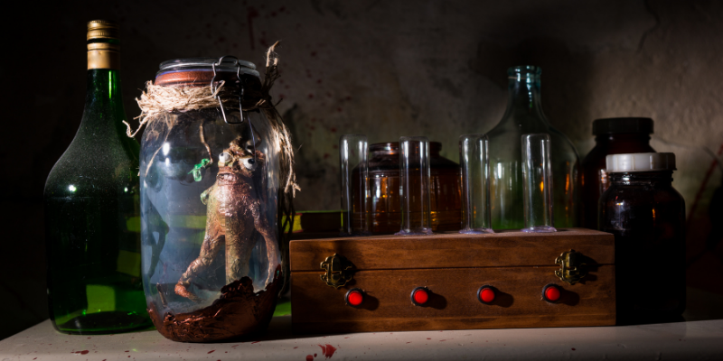 voodoo doll in jar surrounded by jars boxes and other spooky items