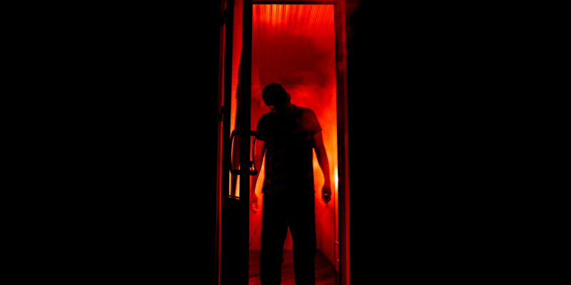scary guy standing inside open doorway with fog and red light coming from behind him